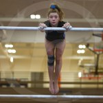 Sophomore Krissy Rubesch looks up as she prepares to dismount off of the high bar. Photo by Sarah Golder