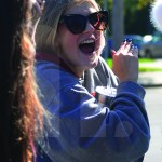 Junior Ella Smith yells for cars to stop by the sale. Photo by Bella Wolfe