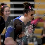 Junior Avery Wilson tightens the bar before warming up her bar routine. Photo by Kate Nixon