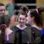 Senior Abby Gorman congratulates freshman Jill Rice after Rice performs her beam routine. Photo by Kate Nixon