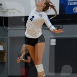 Junior Addie Dunbar serves the ball over the net during a close match. Photo by Elise Madden