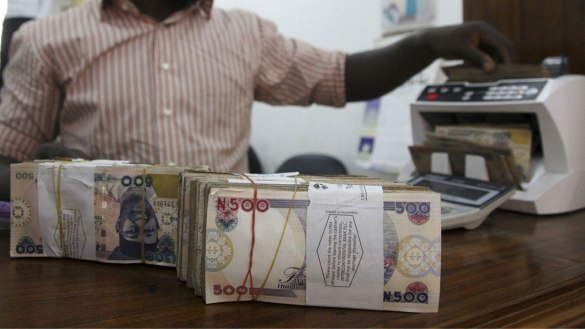 Man counting money for online businesses and FG's ₦50bn Credit Facility (TCF)