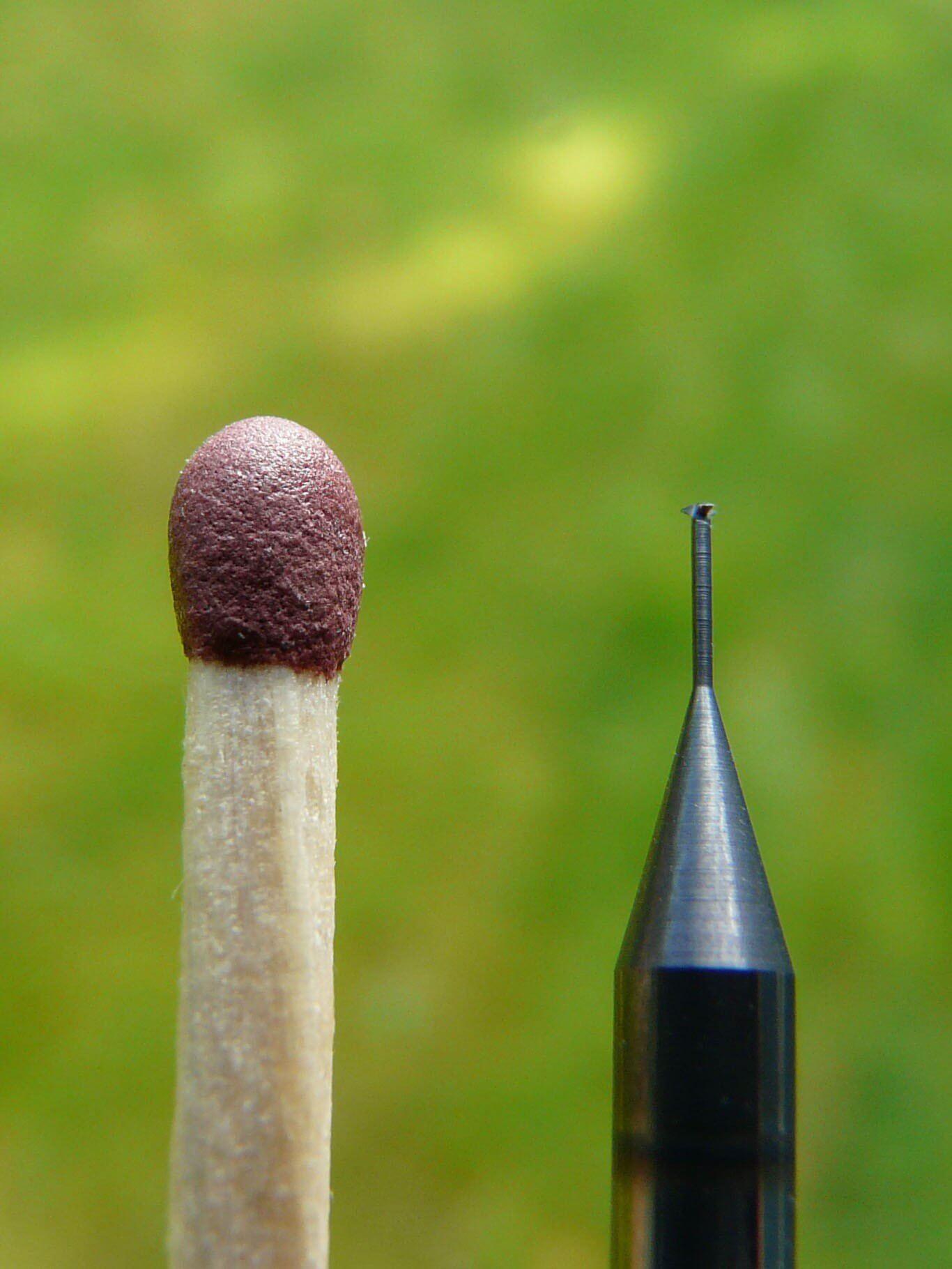 Storleken på en micro gängfräs för M1 jämförs med en tändsticka.