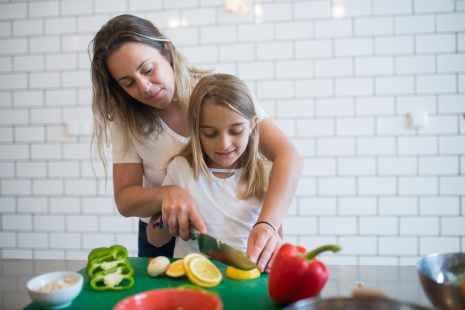 girl in white tank top assisting daughter to chop lemon