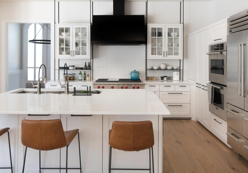 white kitchen with black metal hood and shelving and Galley sink