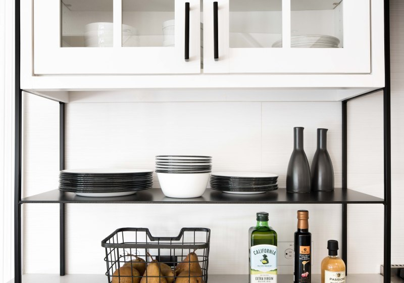 Glass-front cabinetry and open metal shelving in black and white kitchen