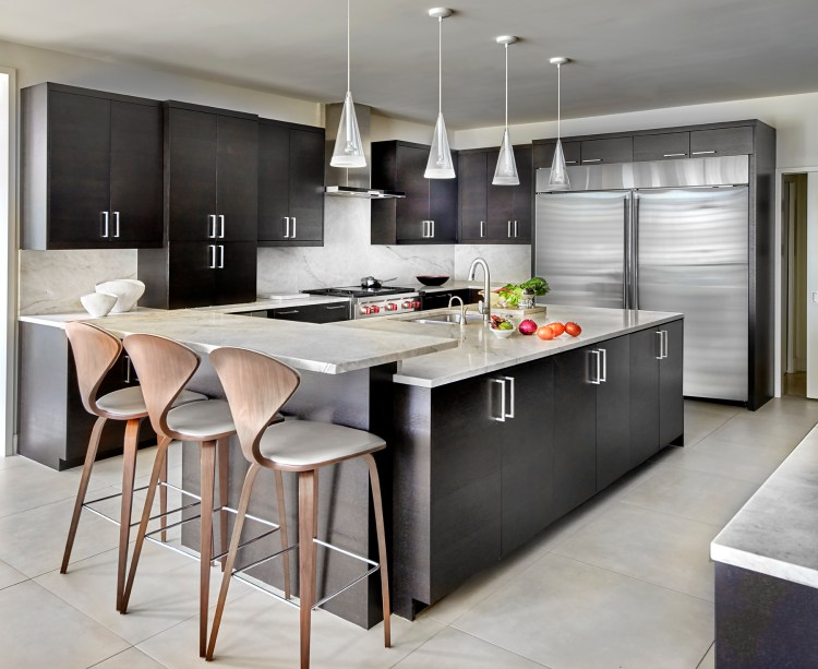 Making salsa in a warm contemporary Dallas kitchen with dark oak cabinetry and Cherner bar stools