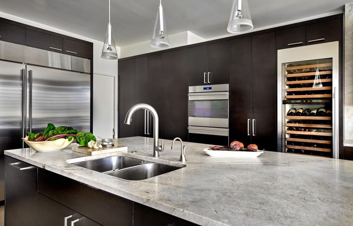 warm contemporary kitchen with dark oak cabinets and Sub-Zero Wolf appliances and quartzite countertops