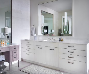 Organic master bath with white contemporary cabinets and sconces on large mirror