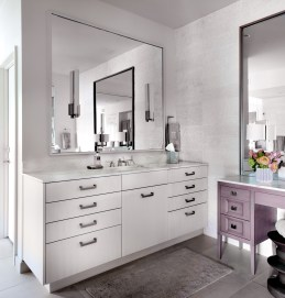 Organic master bath with white contemporary cabinets and sconces on large mirror and seated wood makeup vanity