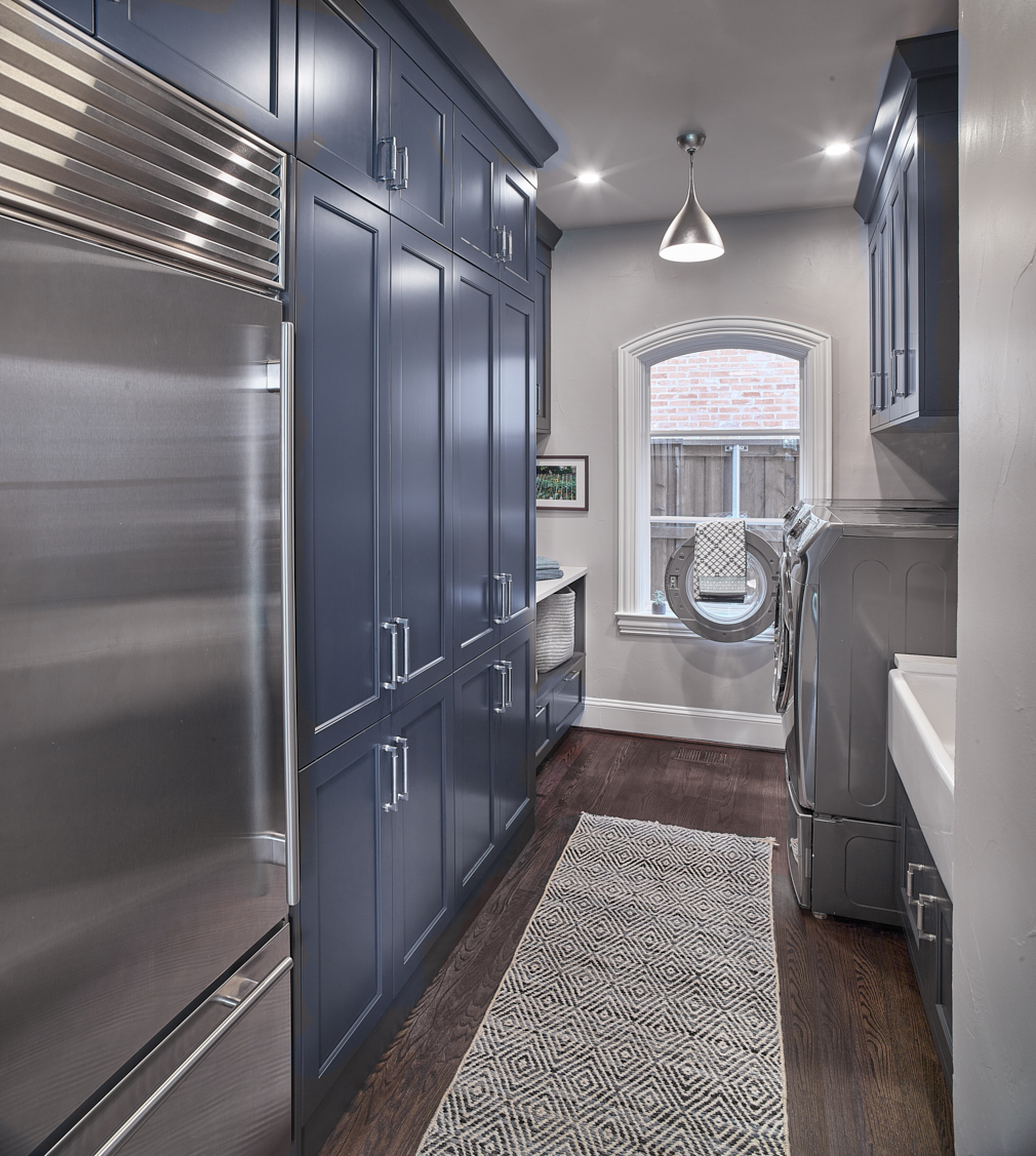 navy blue laundry room cabinets with refrigerator and rug