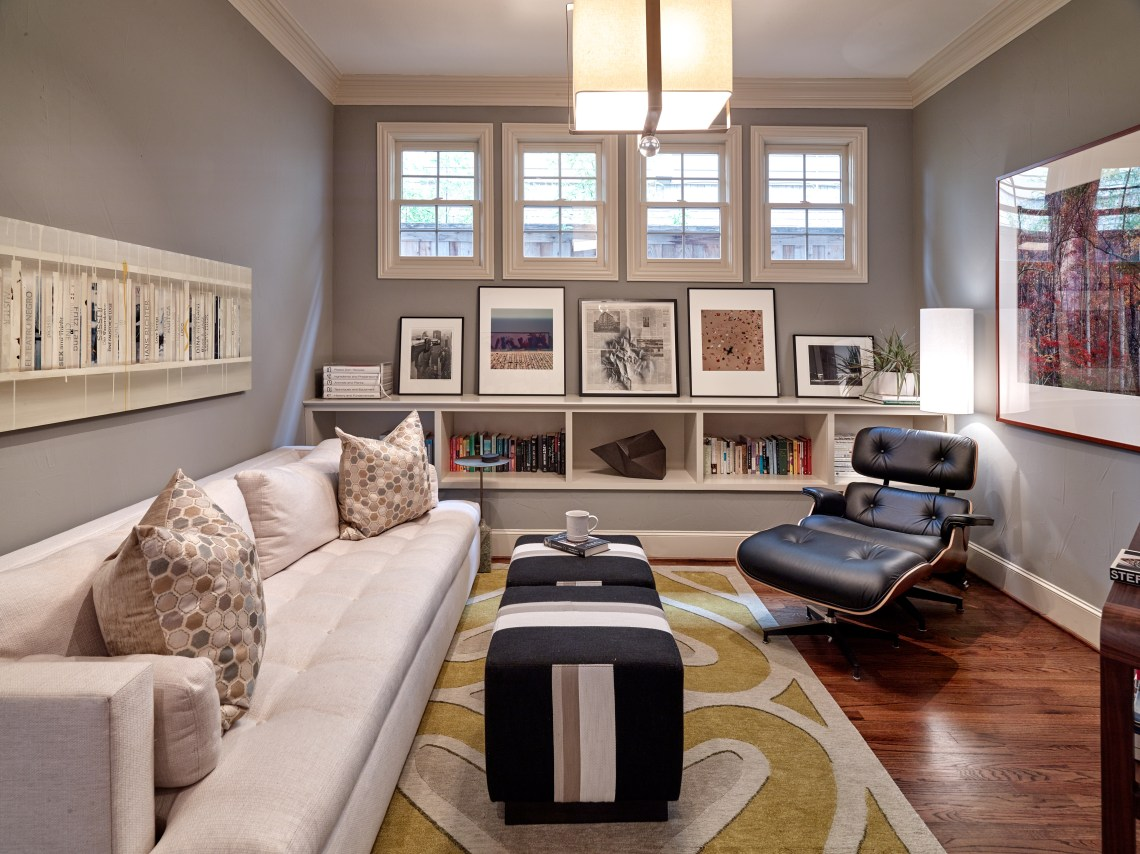Family room with Eames lounge chair and white sofa and two striped ottomans with bookshelf and leaning art
