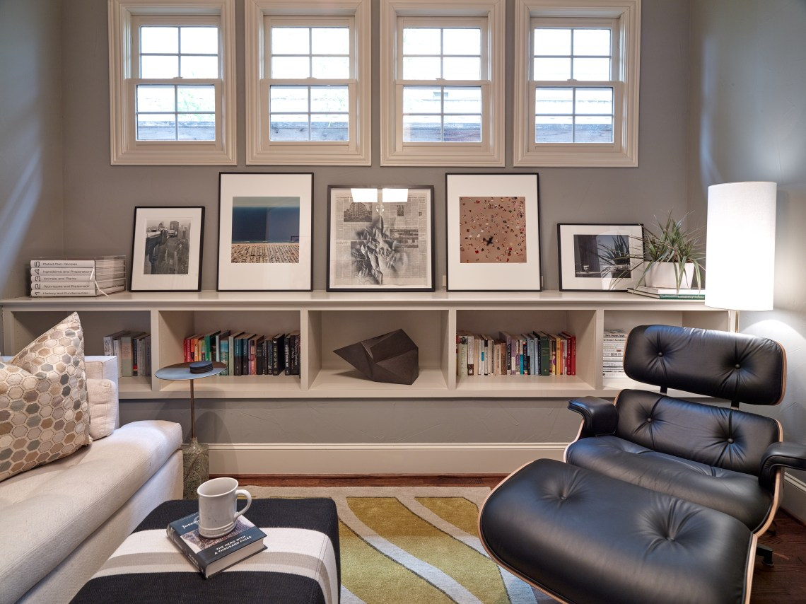 Family Room with Eames lounge chair with colorful shelf styling and yellow rug and striped ottomans