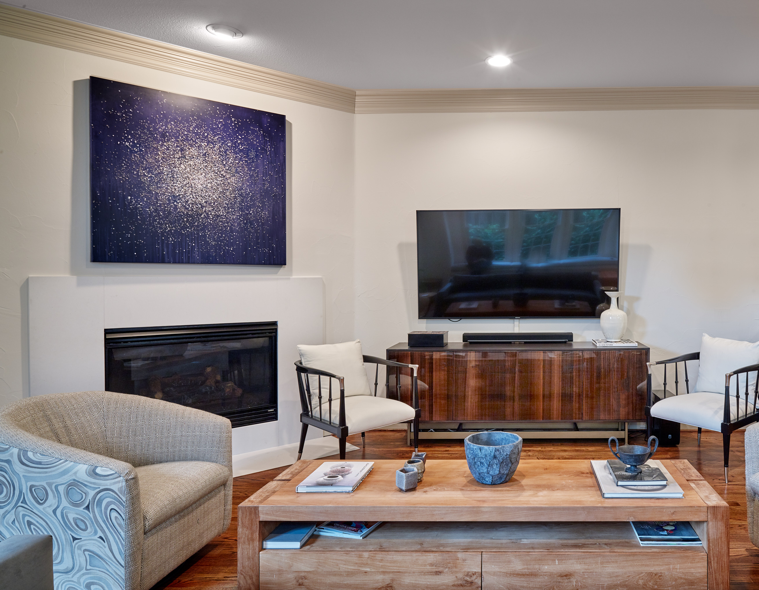 Blue art above contemporary fire place in living room with media console