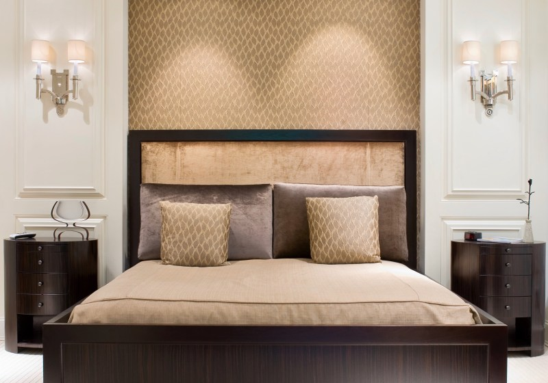 traditional bedroom with gold bedding and fabric headboard