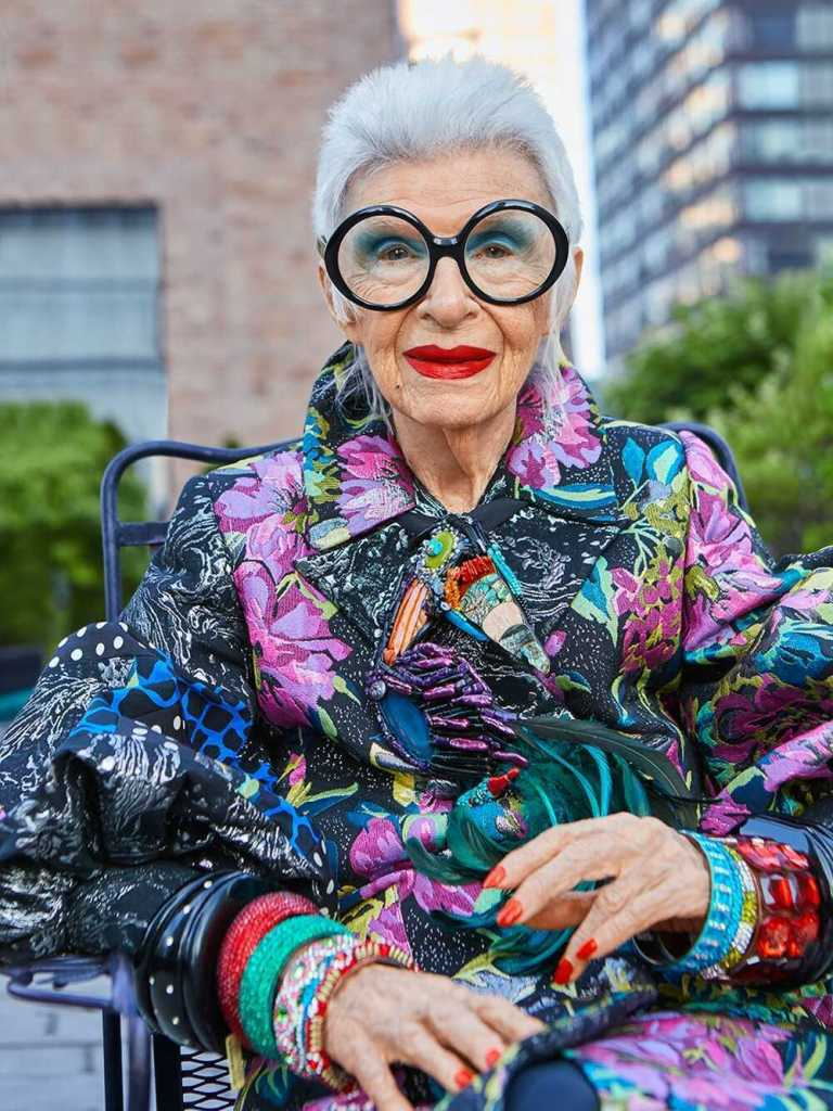 Iris Apfel takes maximalist style to soaring heights. With crazy glasses, jewelry that weighs more than she does, and an overall flee-market-slash-desert-bazaar-chic look, it's easy to acknowledge that the woman is brimming with style inspiration. The 94-year-old has an attitude that is contagious and a style that will stand the test of time. Let's enter the colorful, beautiful, chaotic world of all things Iris Apfel aka the queen of maximalism... eek, we are excited!