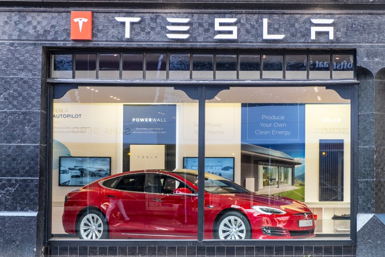 Red Tesla Model S inside a showroom.