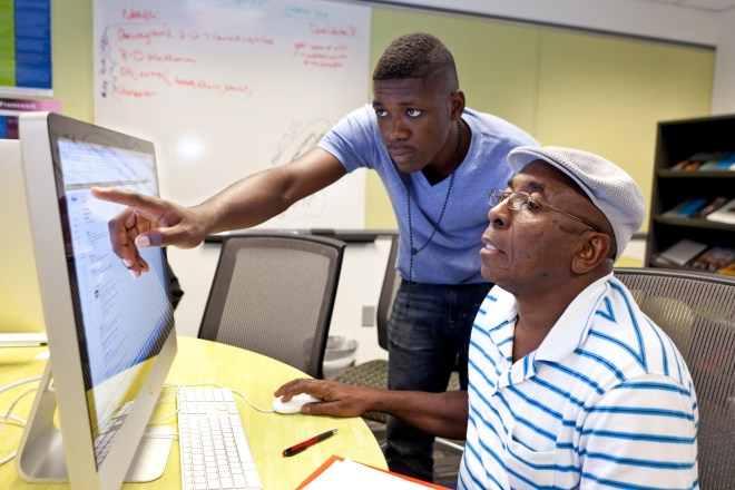 A JCSU student trains an elder on the use of technology in the MACMAS Lab