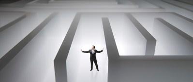 Man seeking financial security lost in maze raising arms in frustration