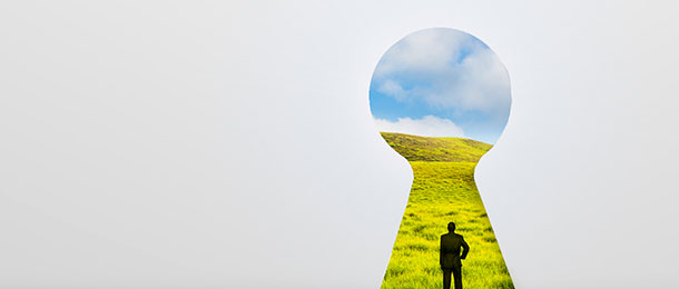 Image of a person standing in a field from the perspective of looking through a keyhole.