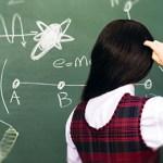 A woman looks at a blackboard.