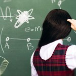 A woman looks at a blackboard.