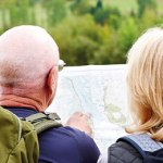 Older hikers look at a map.