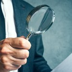 Tax inspector investigating financial documents through magnifying glass.