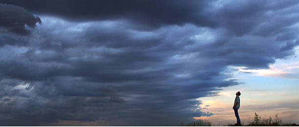 A person stands underneath cloudy skies.