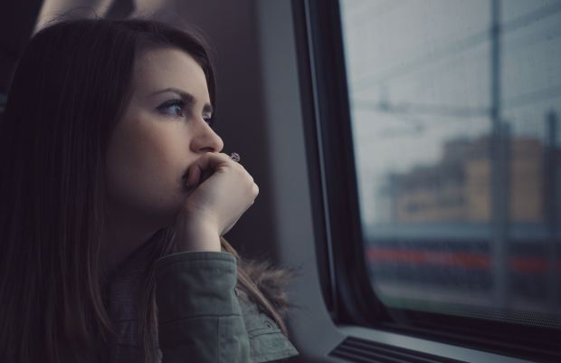 A woman sits on a train, looking anxious, stressed