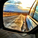 Rear view of a road from side mirror.