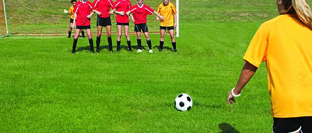Female soccer player taking free kick