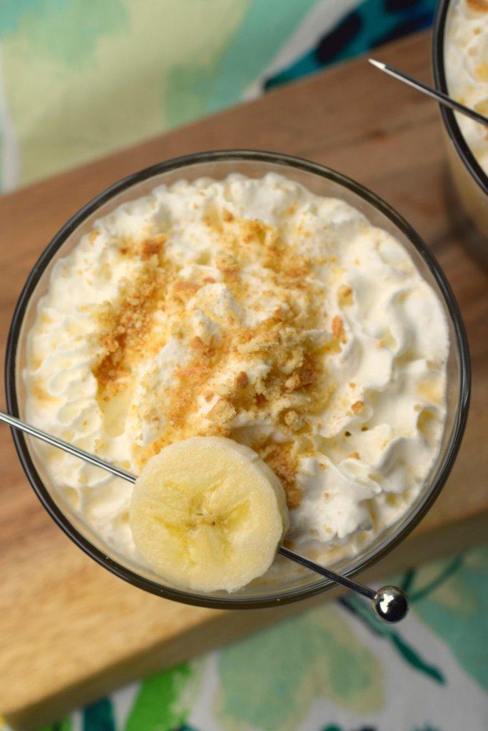 overhead shot of glass with sliced banana garnish on whipped cream