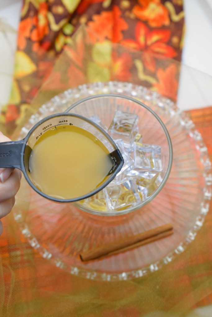 peach nectar being poured into glass for cocktail