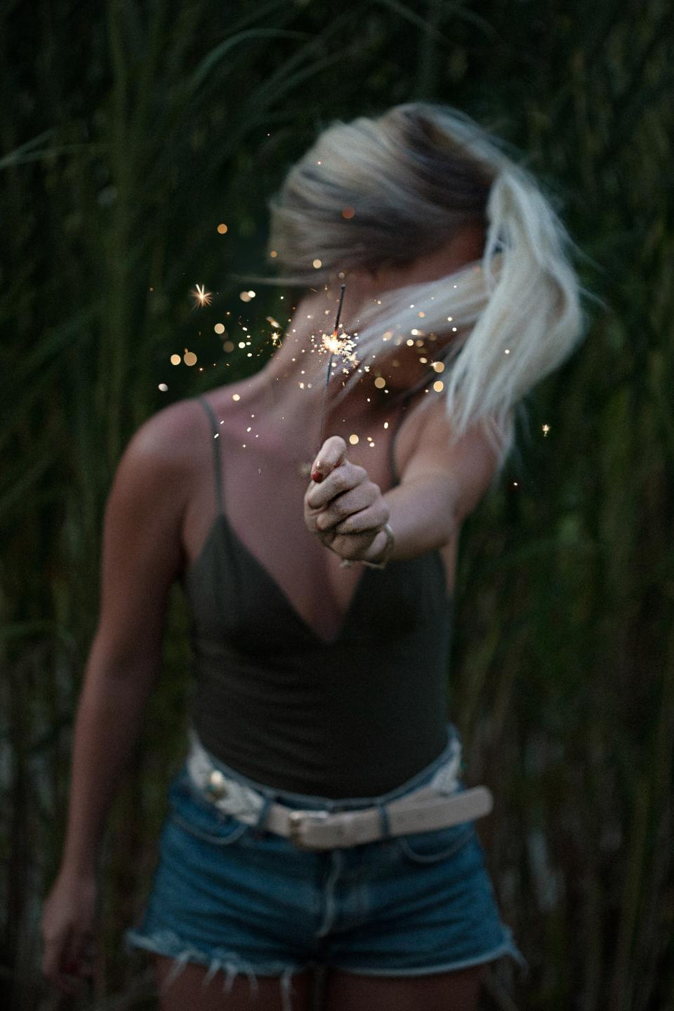 woman, girl, lady, people, stand, fashion, style, hold, out, sparklers, fireworks, sparkle, crackle, sparks, light, orbs, celebrate, field, leaves, still, bokeh
