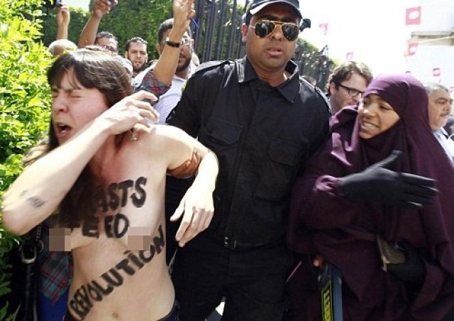 Police officers detain an activist from the women's rights group FEMEN during a protest in front of Tunisia's Ministry of Justice in Tunis
