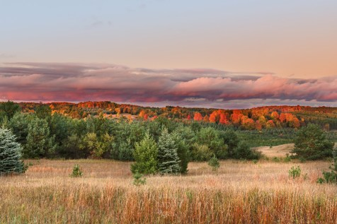 A rolling hillside in Antrim County, Michigan, blazes red under the last light of a stormy day
