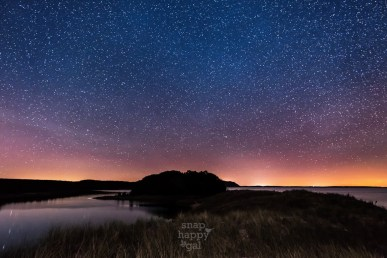 Twilight and countless stars glow above North Bar Lake and Lake Michigan