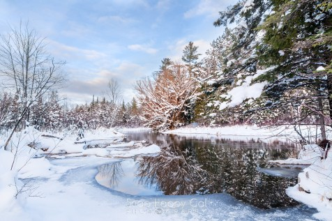 Photo: snowy winter river reflections, blue sky