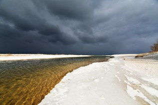 Photo: high-contrast cloud and snow near a river