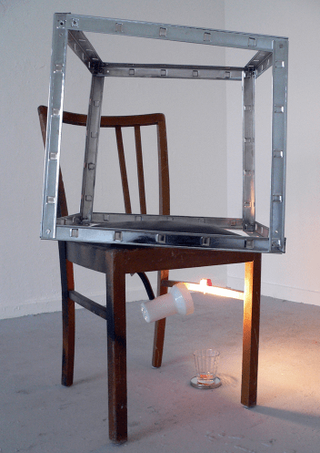 WIR MACHEN ES UNS SCHÖN (DESTILLATOR) / WE MAKE IT OUR BEAUTIFUL (distiller). 2009, chair, metal, lamp, mirror, glass filled with alcohol Praline, 70 x 110 x 40 cm / WIR MACHEN ES UNS SCHÖN (DESTILLATOR). 2009, Chaise, métal, lampe, miroir, verre, l'alcool de praline, 70 x 110 x 40 cm