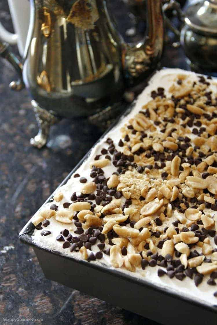 Chocolate Peanut Butter Lasagna in pan with whipped topping, chocolate chips, and peanuts