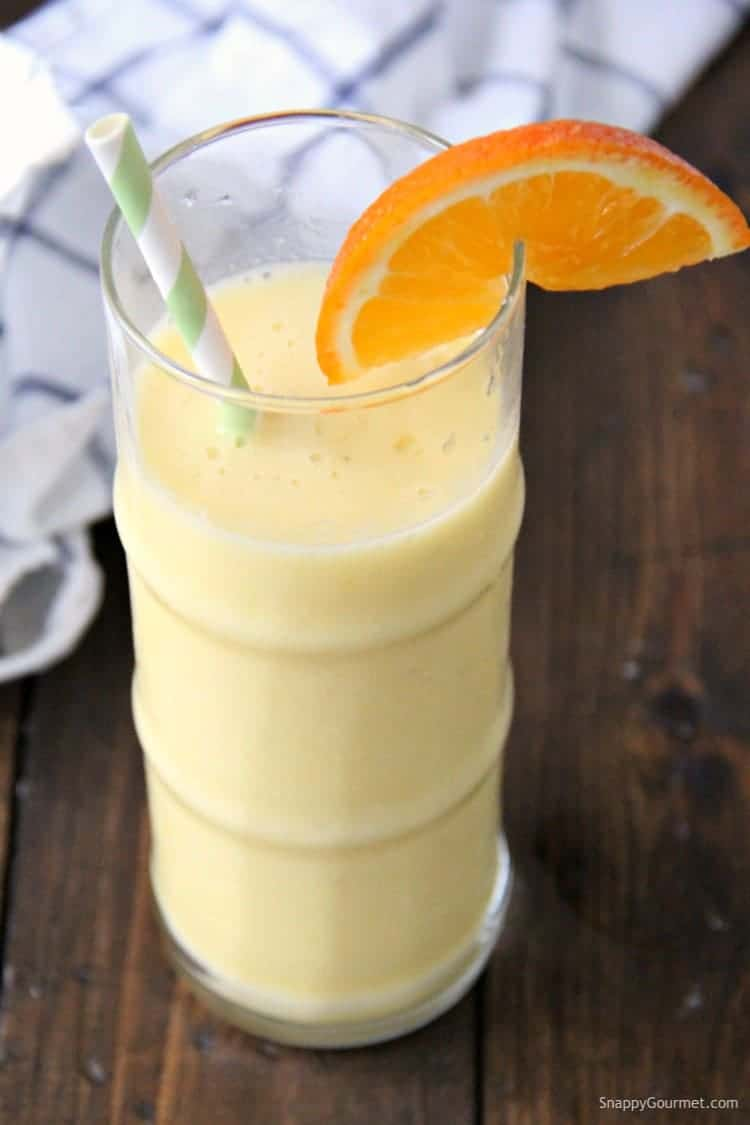smoothie in tall glass with straw and orange slice