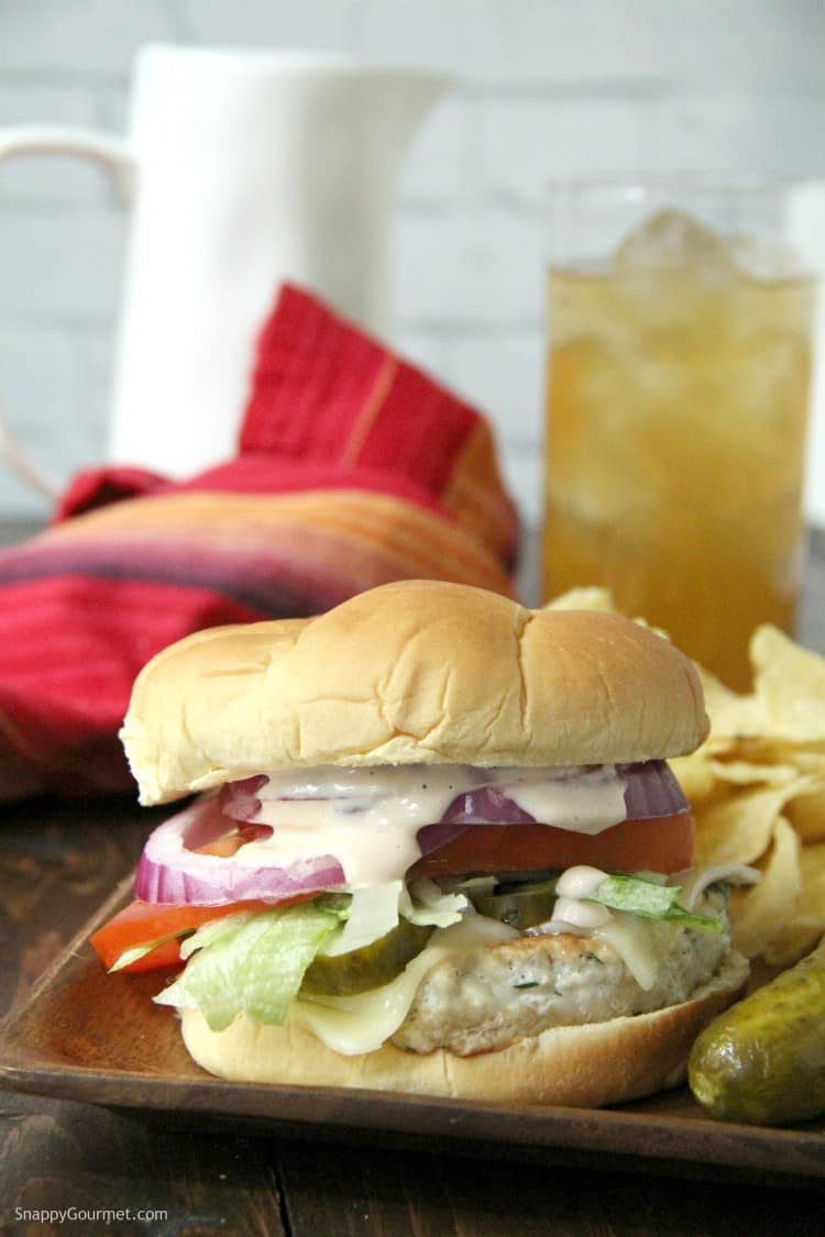 dill pickle chicken burger with napkin and rink
