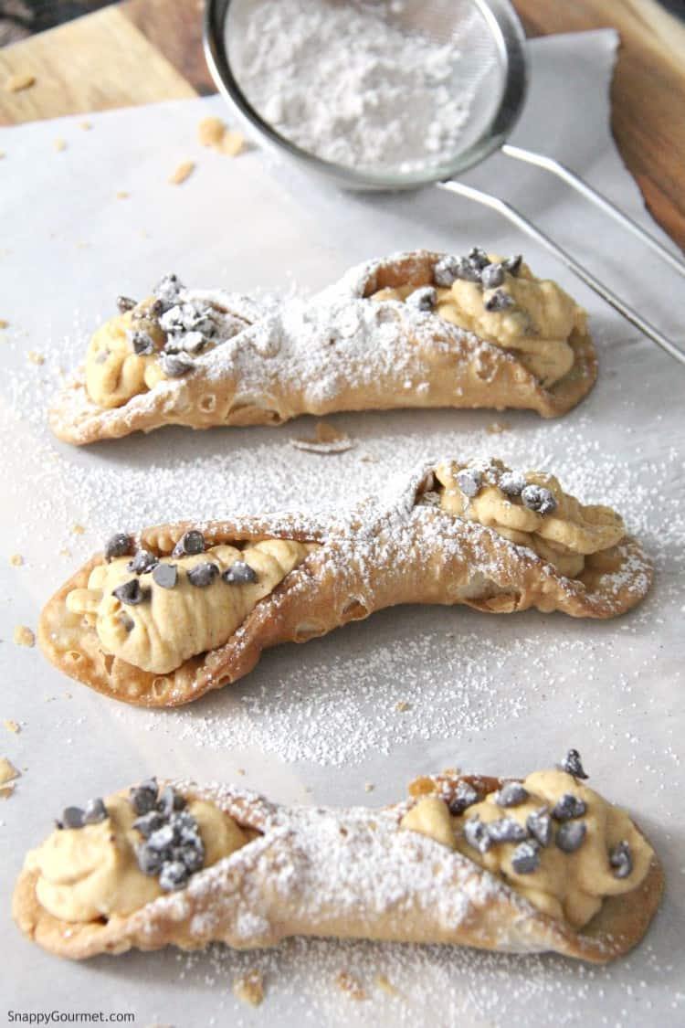 pumpkin cannoli being dusted with powdered sugar