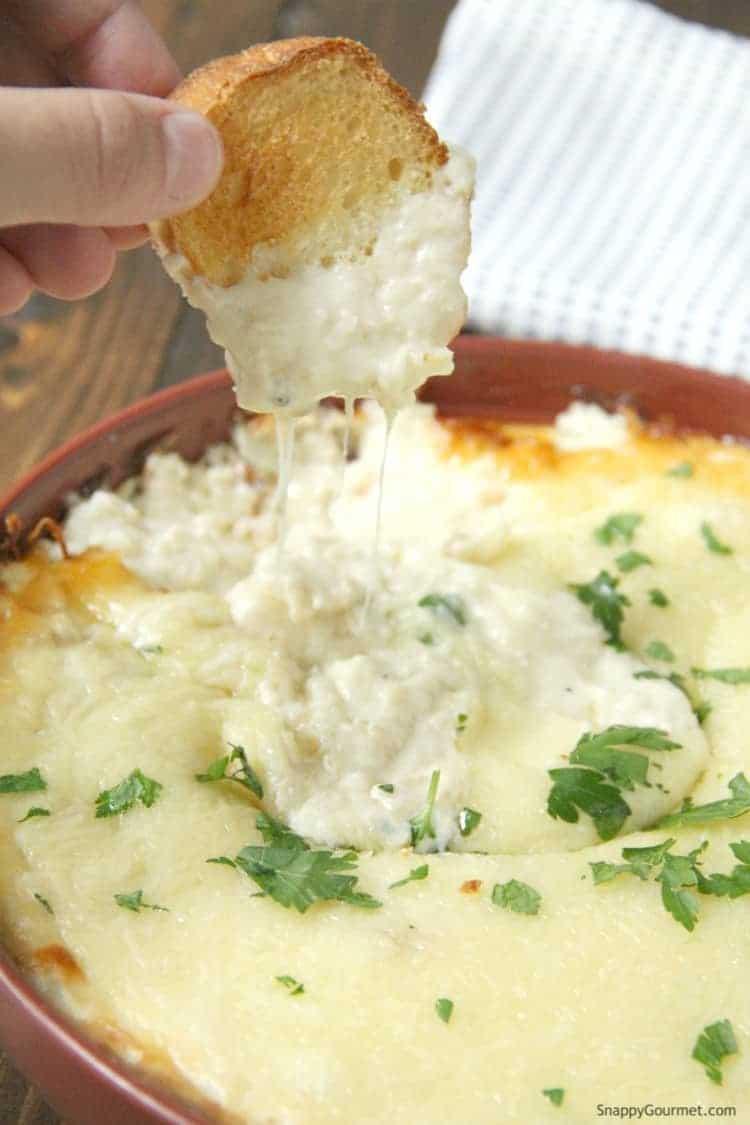 cheesy Chicken Alfredo Dip in baking dish with crostini
