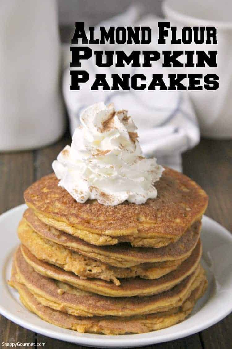 easy gluten free pumpkin pancakes stacked on plate with whipped cream and pumpkin spice