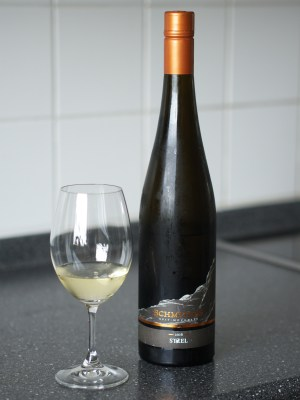 Front view of the Steel bottling from Weingut Schmitges, with glass of wine.