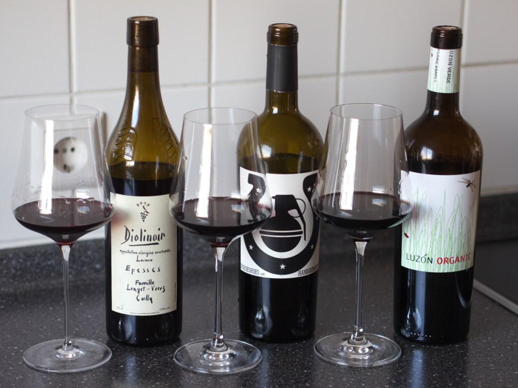 Three glasse and three bottles of red wine.