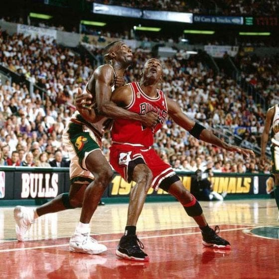 Michael Jordan of the Bulls, wearing the Jordan XI 'Playoff' boxing out Shawn Kemp of the Sonics,wearing the Reebok Optix - Image via Hk-Kicks